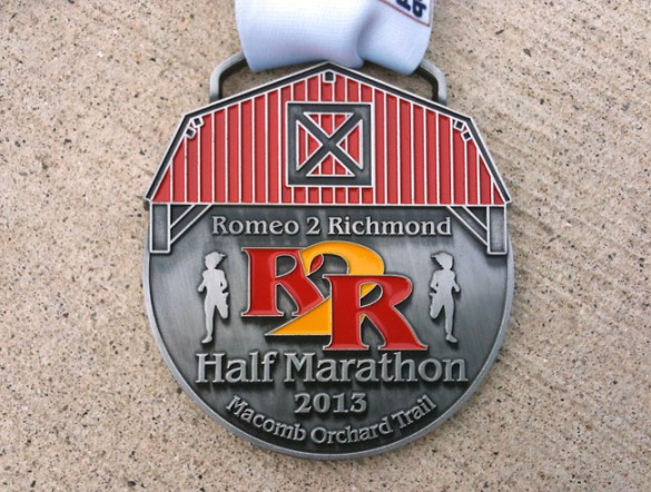 The medal features the barn-like covering over M-53 at the start of the race